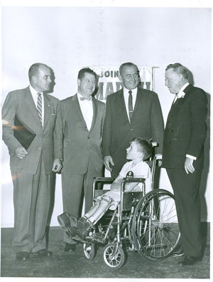 A child in a wheelchair with 4 adult men