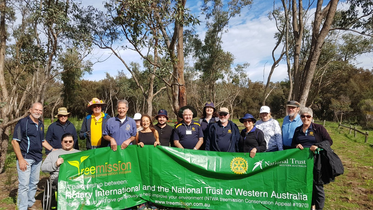 A group of happy tree planters with the Treemission banner