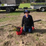 Jan is kneeling with a bucket of seedlings