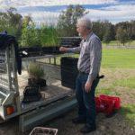 Volunteer organising seedlings on the back of the trailer