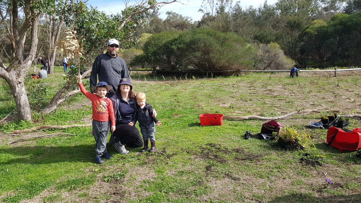 A family of two parents and two young boys enjoying tree planting